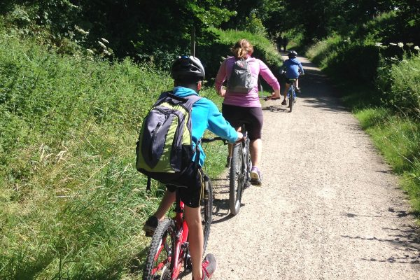 A family on mountain bikes cycling along a gravel path.