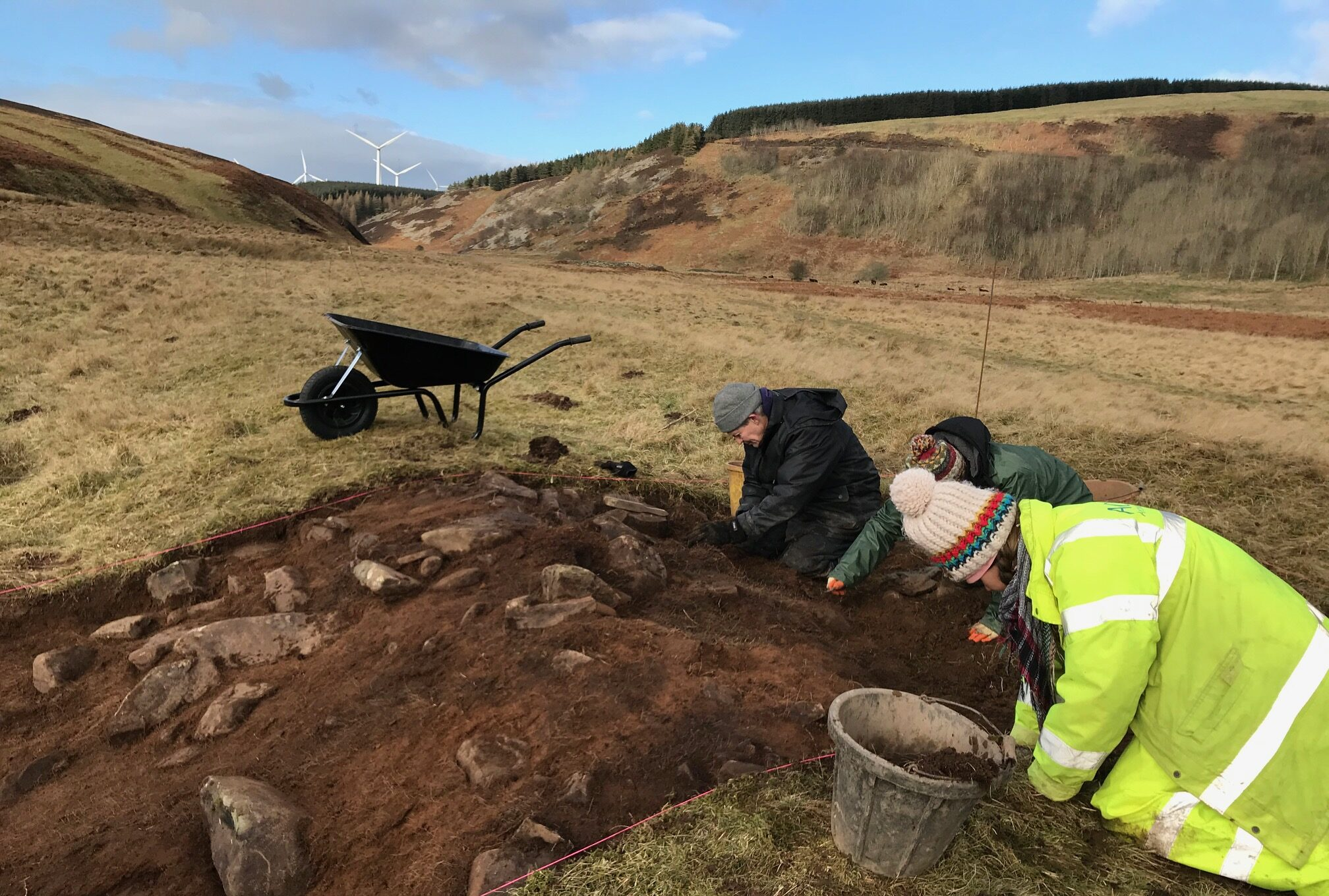 archaeologists and volunteers digging a trench in a valley