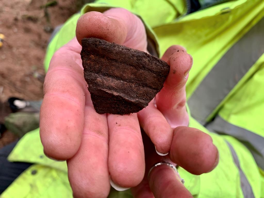 A sherd of rough, unglazed pottery in someone's hand
