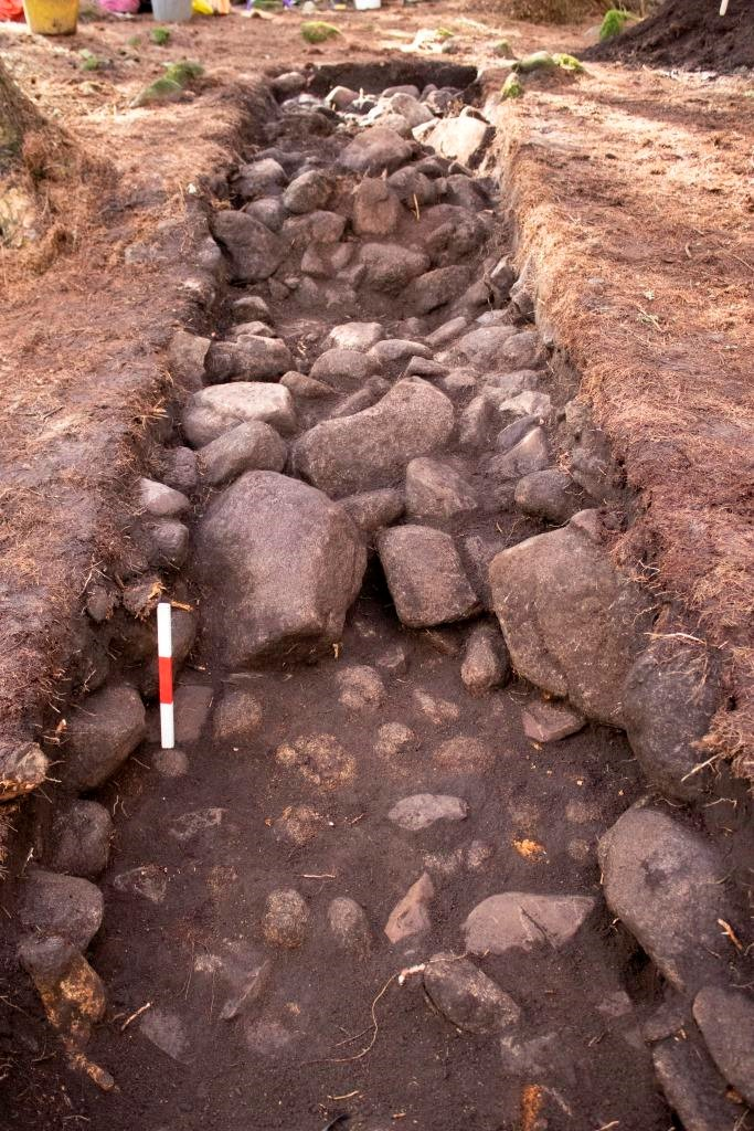 A long trench with stones forming the body of the cairn in the background, and a stony, possible trampled ground surface in the foreground
