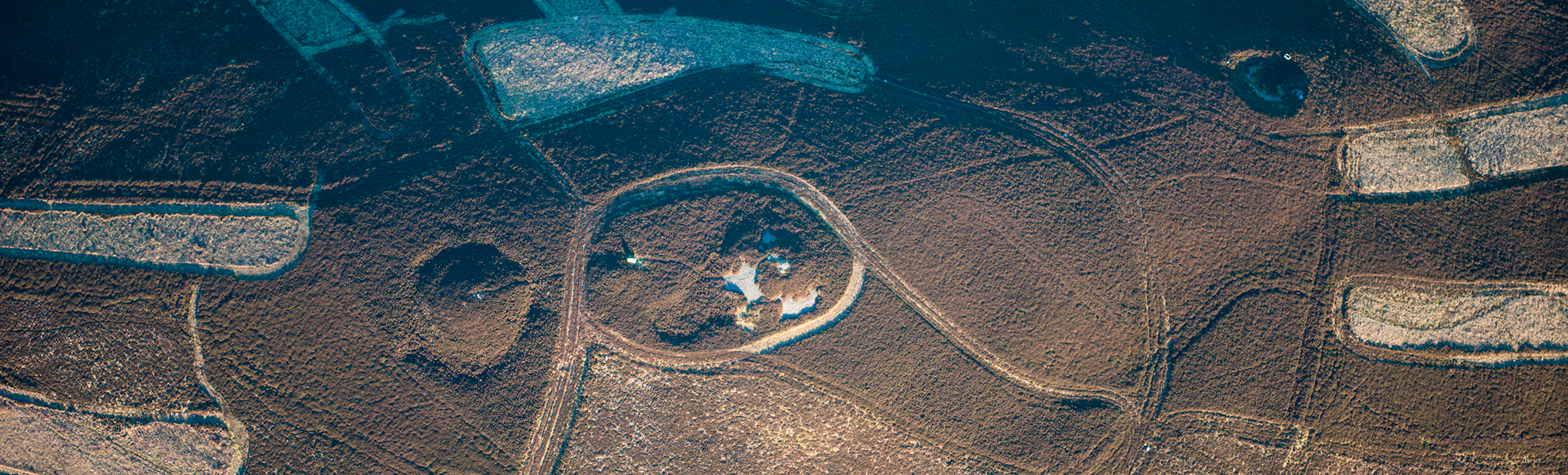 Oblique aerial view of the cairns on Dirrington Great Law, surrounded by heather/moorland cut by paths (c) Historic Environment Scotland