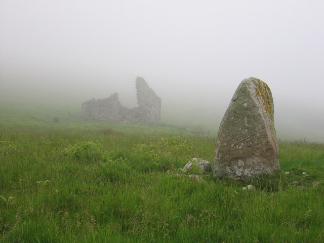 A standing stone in the foreground, with a ruinous building in the mist behind