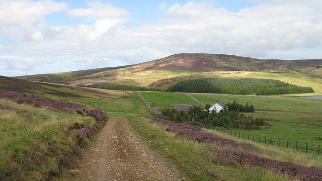 Rough track across open landscape, with two houses to the right of the track and heather-covered hills in the distance