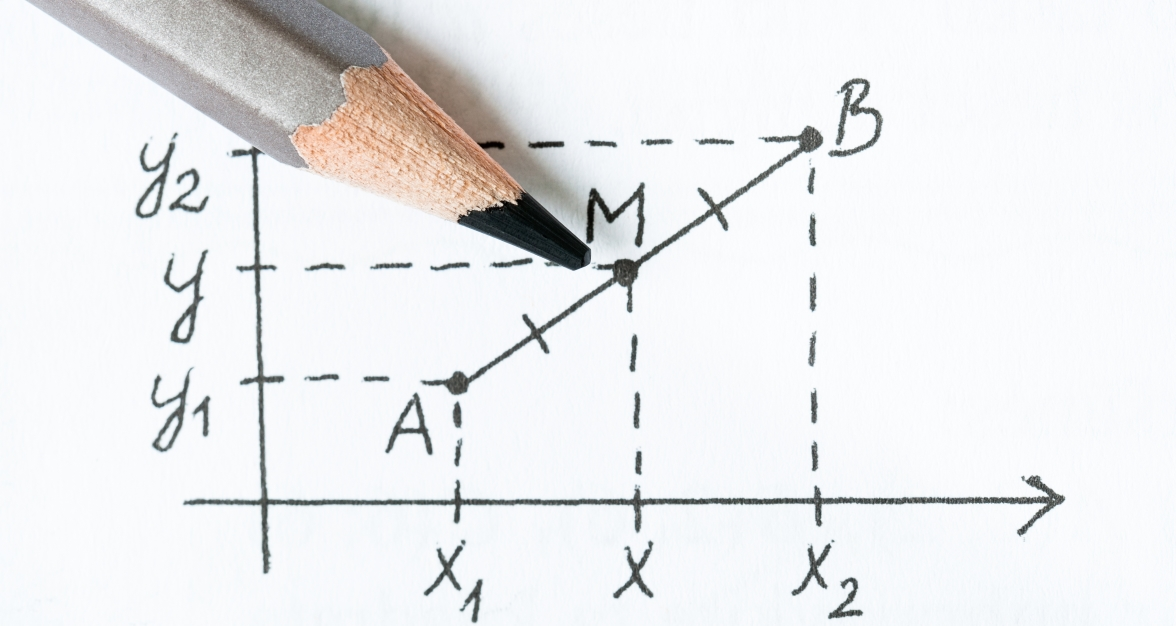 A pencil over paper, showing a graph