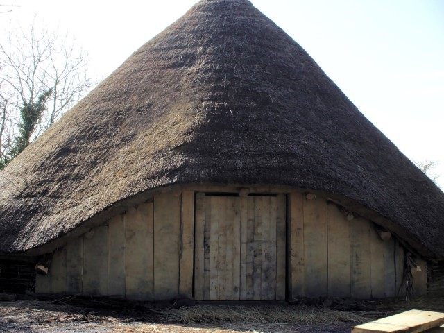 Rreplica roundhouse with conical thatched and wooden planking around the walls