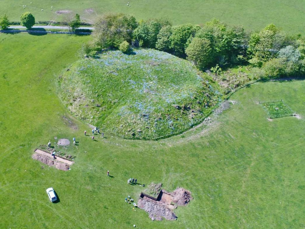 Aerial photograph showing a round, grass-covered mound on which the remains of the castle sit, with trenches open in the flat grassy field in front of the motte