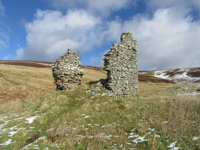 Ruinous remains of castle walls in open landscape