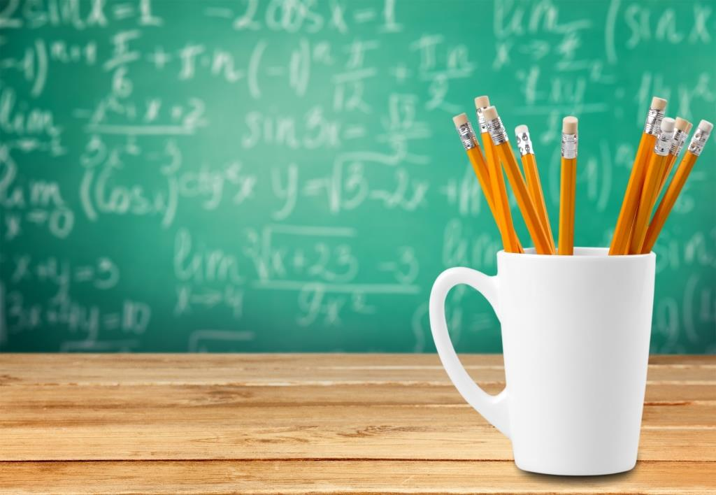 A mug full of pencils in front of a chalkboard