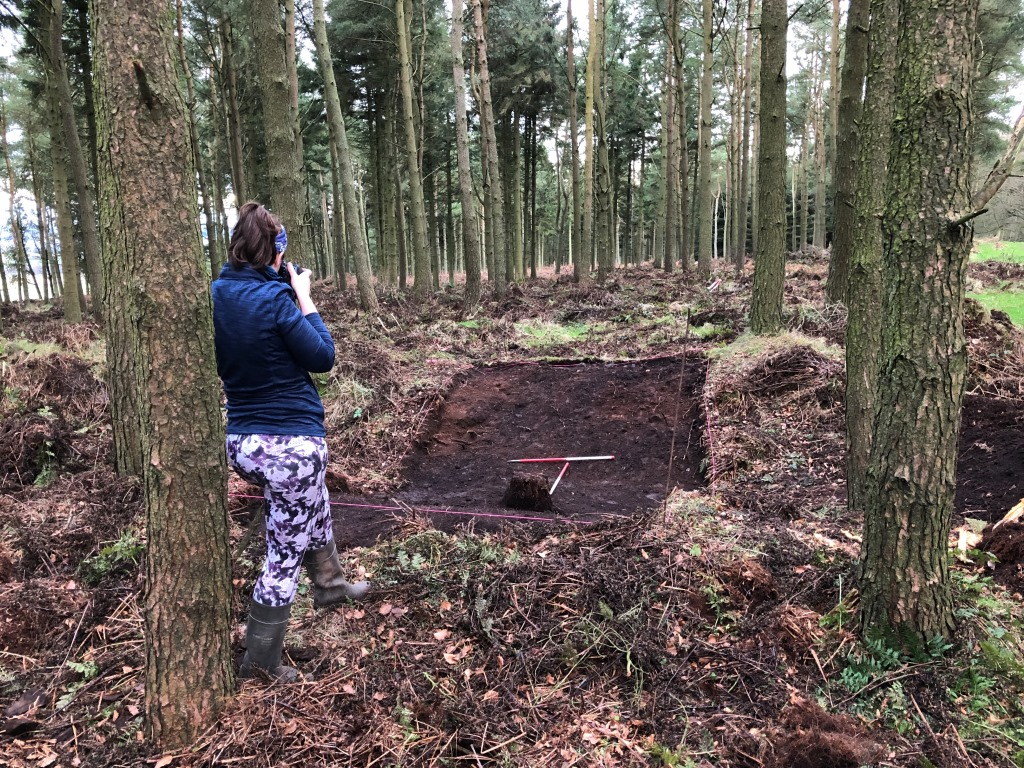 Image of a female archaeologist in forestry, taking a photograph of a ditch which has been cleared of vegetation where a trench has been laid out
